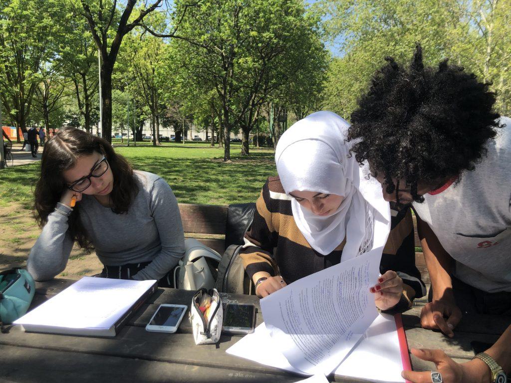 Tre studenti che studiano al parco in primavera